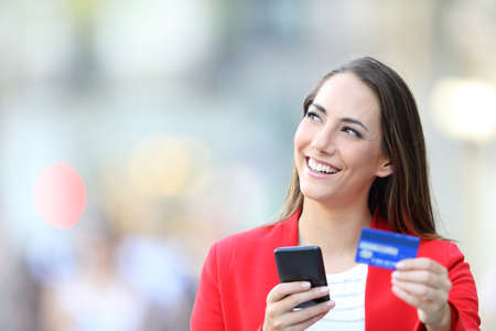 Happy woman in red holding credit card and smart phone thinking looking at side in the street Stock fotó