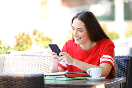 Happy student in red texting on smart phone sitting in a coffee shop terrace