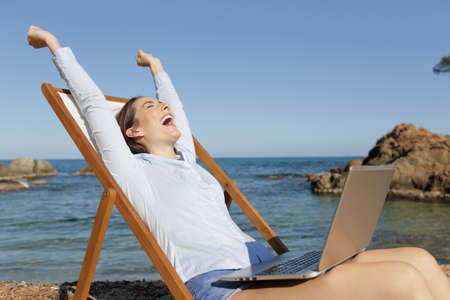 Excited entrepreneur with laptop raising arms celebrating success sitting on a deck chair on summer vacation on the beach