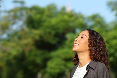 Happy mixed race woman breathing deeply fresh air in a park or forest a sunny day