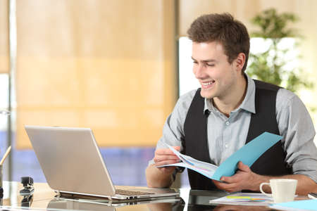 Happy worker comparing laptop online content and paper documents at office
