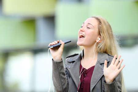 Happy teenage girl singing karaoke using smart phone and earphones outdoors