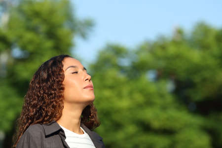 Relaxed mixed race woman breathing deeply fresh air in a park or forest a sunny day