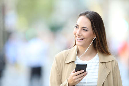 Front view portrait of a happy woman wearing earbuds listening to music on smart phone looking at side in the street