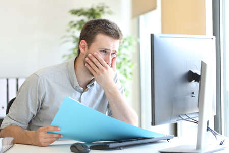 Worried businessman discovering mistake comparing document information and computer content at office