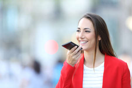 Happy woman in red using voice recognition on smart phone to dictate message in the street Stock Photo