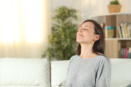 Relaxed woman breathing fresh air sitting on a couch in the living room at home Standard-Bild