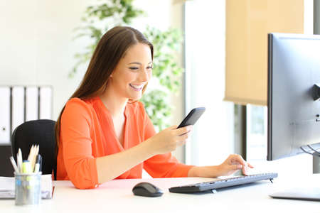 Happy entrepreneur in orange checking smart phone message at office