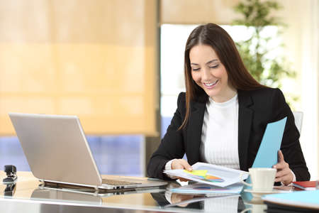Happy executive checking paper documents sitting at office