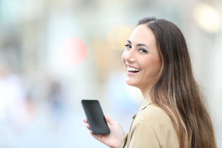 Happy woman holding smart phone looks at camera standing in the street Stock fotó