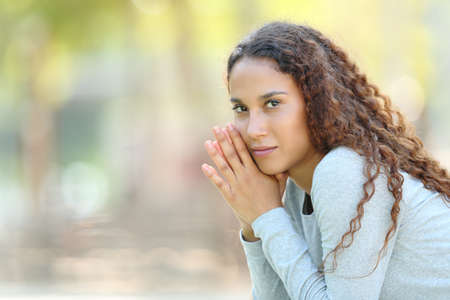 Serious beautiful mixed race woman posing looking at camera in a park