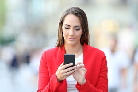Front view of serious woman in red using smart phone walking in the street