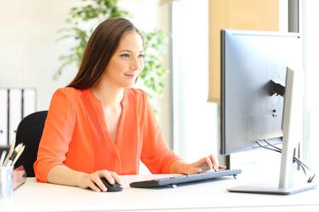Imprenditore soddisfatto in arancione che lavora con il computer desktop in ufficio