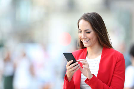 Happy elegant woman in red using smart phone standing in the street