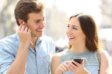 Front view of a happy couple walking listening to music sharing earphones in the street