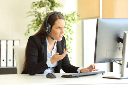 Comercializador de tele enojado atendiendo al cliente en línea en la oficina