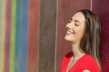 Portrait of a happy woman in red leaning on a colorful wall in the street