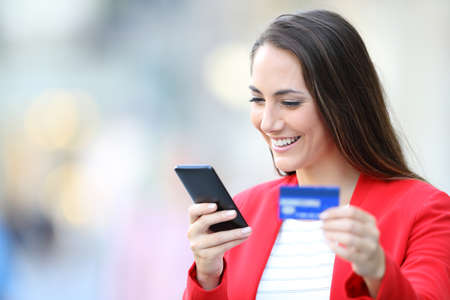 Happy woman in red buying on line with smart phone and credit card in the street Stock fotó