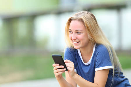 Happy teenage girl holding phone looking at sidesitting in an university campus Stock fotó
