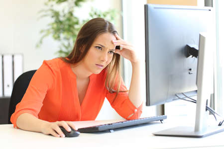 Worried entrepreneur checking bad news on computer at office