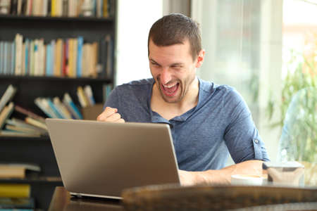 Excited adult man finding laptop online content celebrating success sitting in a bar or home