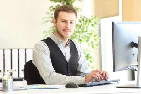 Ejecutivo seguro posando mirando a la cámara con las manos en el teclado de la computadora en la oficina Foto de archivo