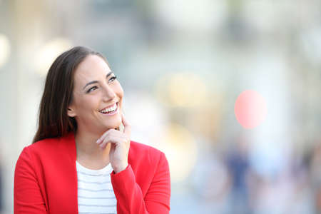Front view portrait of a happy woman in red thinking looking at side outdoors in the street Stock Photo