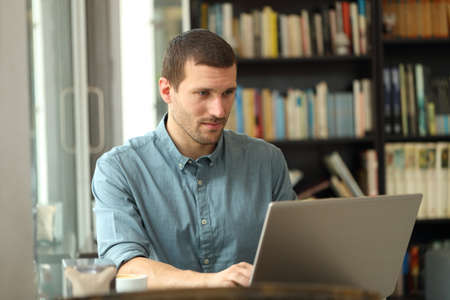 Serious adult man writing on laptop entering data sitting in a coffee shop or home