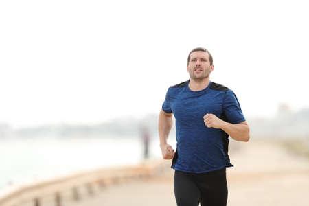 Hübscher Läufer rennt in Richtung Kameratraining am Strand