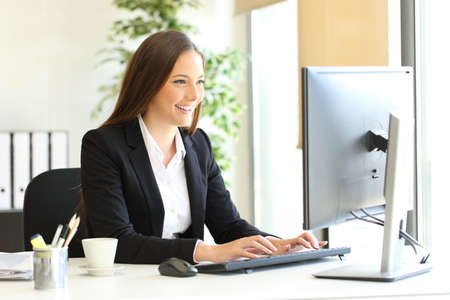 Szczęśliwy dyrektor korzysta z komputera wprowadzającego dane w biurze Zdjęcie Seryjne