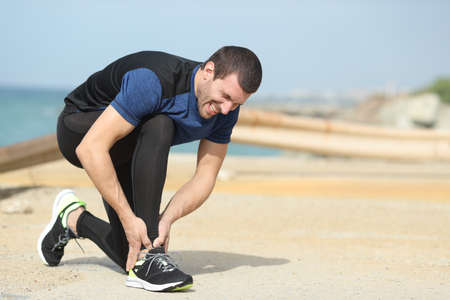 Painful runner complaining suffering ankle ache on the beach after sport