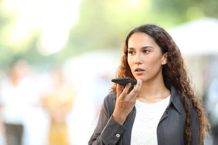 Serious mixed race woman using voice recognition on smart phone walking in the street