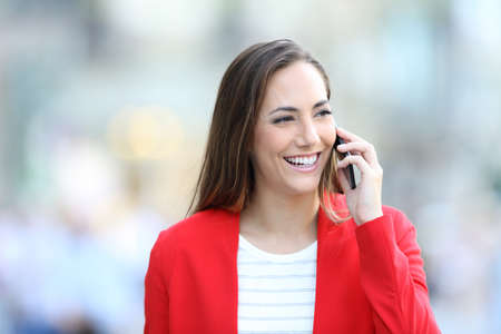 Front view portrait of a happy woman in red talking on phone walking towards camera in the street 免版税图像