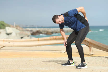 Painful runner complaining suffering back ache after sport on the beach