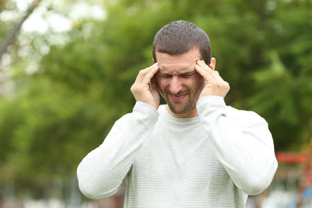 Man suffering migraine complaining standing alone in a park
