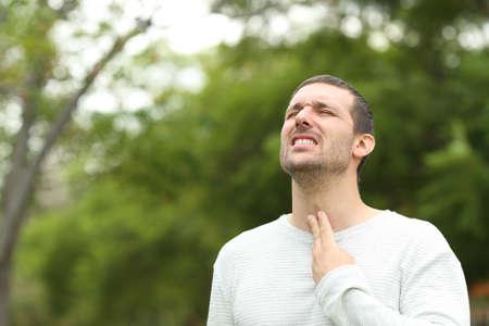 Mann mit Halsschmerzen, der sich beschwert, allein in einem Park zu stehen