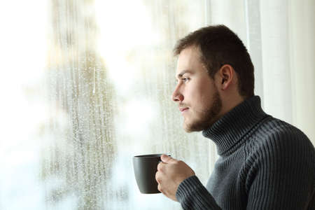 Side view portrait of a serious man holding a coffee mug looking the rain through a window at home