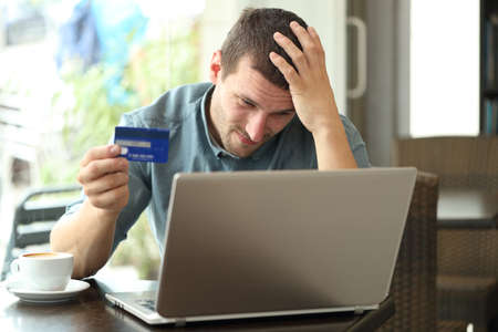 Worried man having problems paying with credit card and laptop sitting in a coffee shop