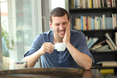 Fronf view portrait of a man complaining suffering tooth ache after drinking hot beverage sitting in a coffee shop