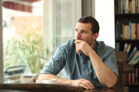 Pensive serious man in a coffee shop looking at side through a window