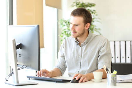 Serious businessman using computer browsing online content at office Banque d'images - 130847045