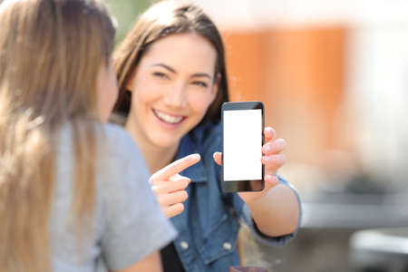 Happy girl shows blak smart phone screen to her friend in the street Imagens