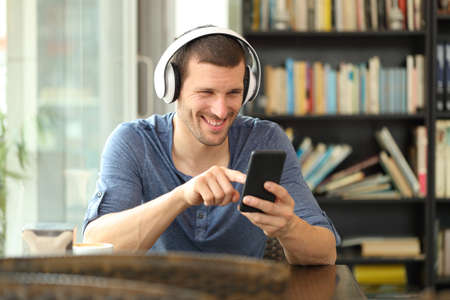 Happy man listening to music with headphones and smart phone sitting in a coffee shop