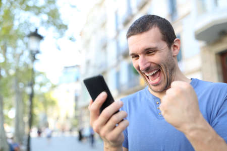 Excited man celebrating good news checking mobile phone content standing in the street Stock Photo
