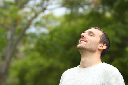 Happy man breathing deeply fresh air in a forest with green trees in the background