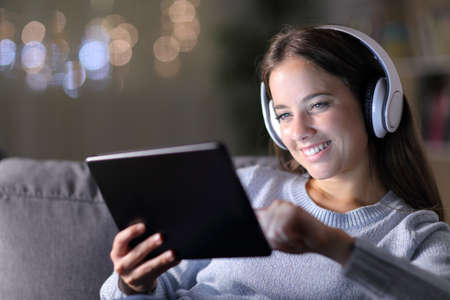 Happy woman wearing headphones uses a tablet sitting on a couch in the night at home