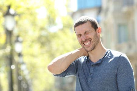Homme adulte stressé souffrant de maux de cou debout seul dans la rue Banque d'images