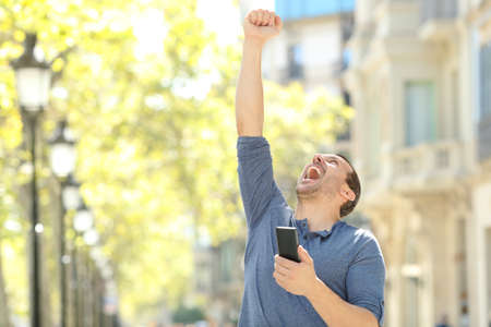 Excited adult man holding mobile phone celebrating success raising arm in the street