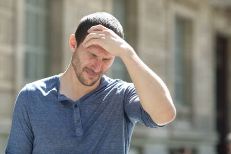 Stressed adult man complaining suffering headache touching head in the street