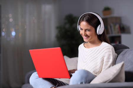 Happy girl wearing headphones using a red laptop sitting on a couch in the night at home